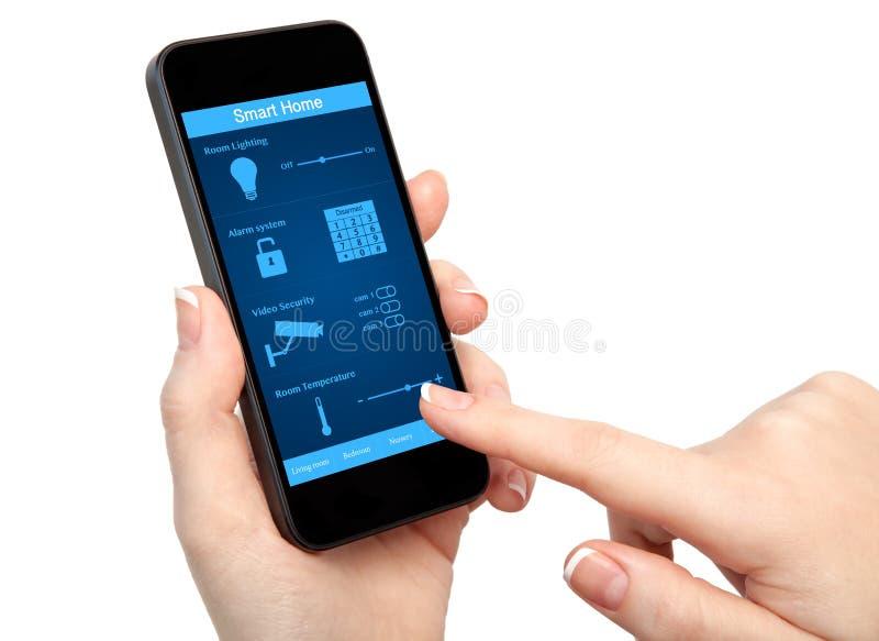 Mão da mulher que guarda o telefone com a casa esperta do sistema fotos de stock royalty free