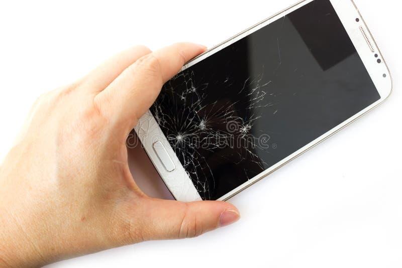 A mão da mulher que guarda o telefone esperto branco quebrado fotografia de stock royalty free
