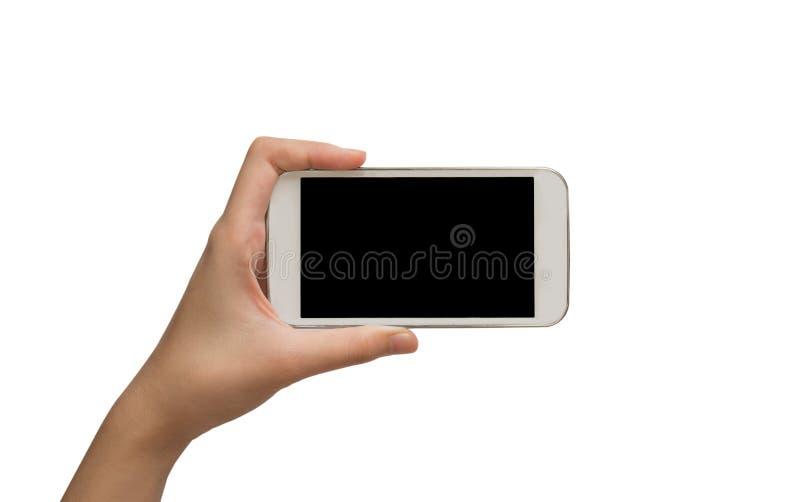 Mão da mulher que guarda o telefone esperto no fundo branco imagem de stock