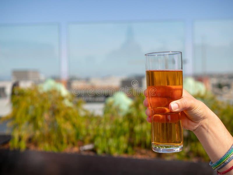 A mão da mulher que guarda o vidro da cerveja de IPA em uma barra do telhado no verão fotos de stock
