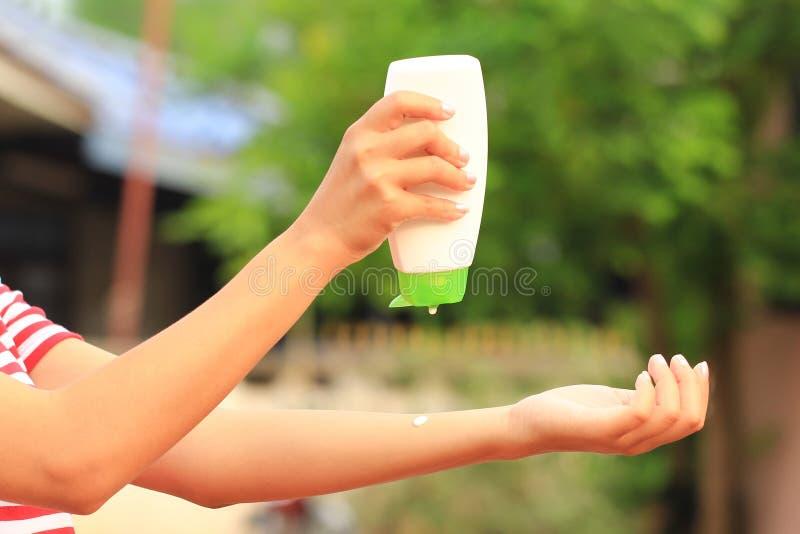 Mão da mulher que guarda a proteção solar no fundo, na proteção do sunblock do spf e no conceito verdes naturais dos cuidados com fotografia de stock royalty free