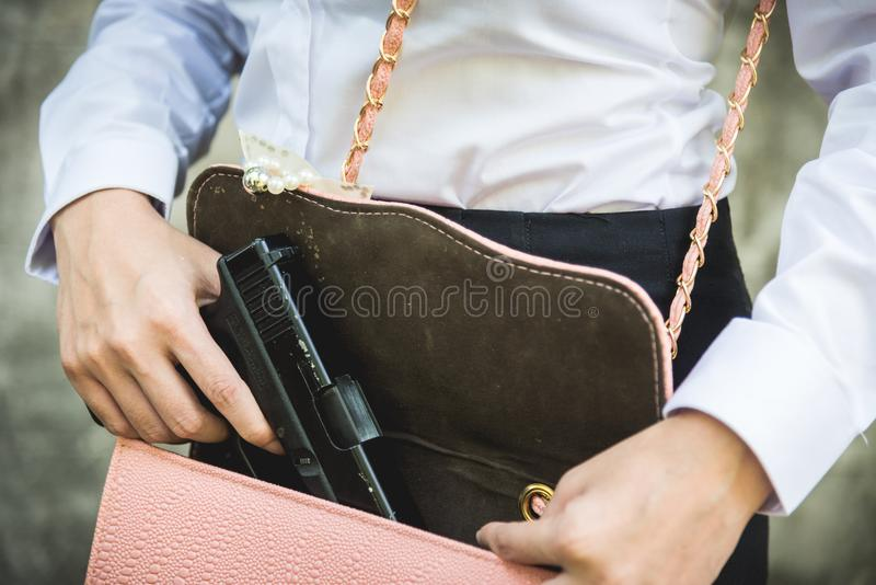 Mão da mulher que guarda a remoção do revólver pequeno de sua bolsa foto de stock royalty free