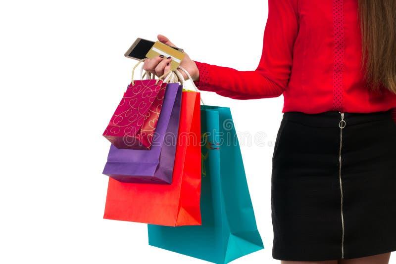 A mão da mulher que guarda sacos de papel coloridos da compra, pacotes, cred imagem de stock