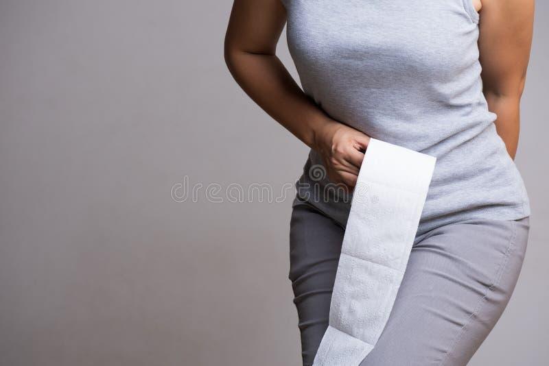 Mão da mulher que guarda seu rolo da parte inferior e do tecido ou do papel higiênico Desordem, diarreia, constipação Conceito do fotografia de stock