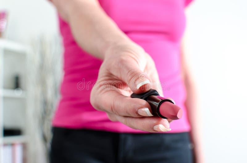 Mão da mulher que guarda um batom imagem de stock