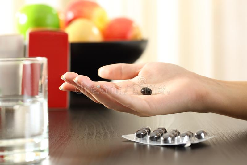 Mão da mulher que guarda um comprimido do complexo da vitamina fotografia de stock royalty free