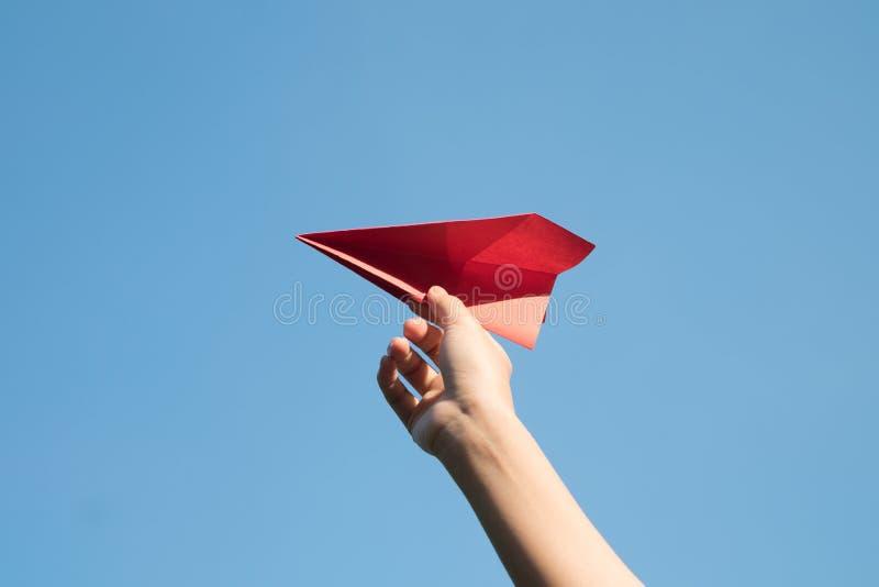 Mão da mulher que guarda um foguete de papel vermelho com um fundo azul brilhante fotografia de stock royalty free