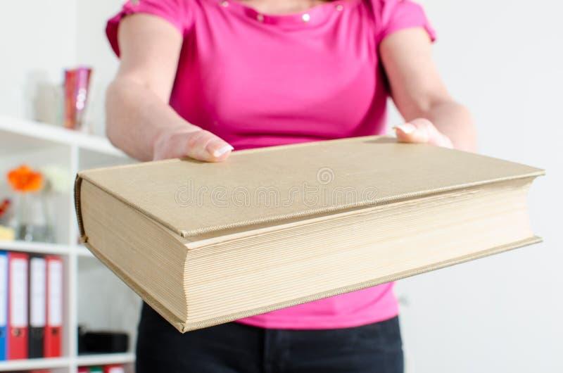 Mão da mulher que guarda um livro foto de stock royalty free