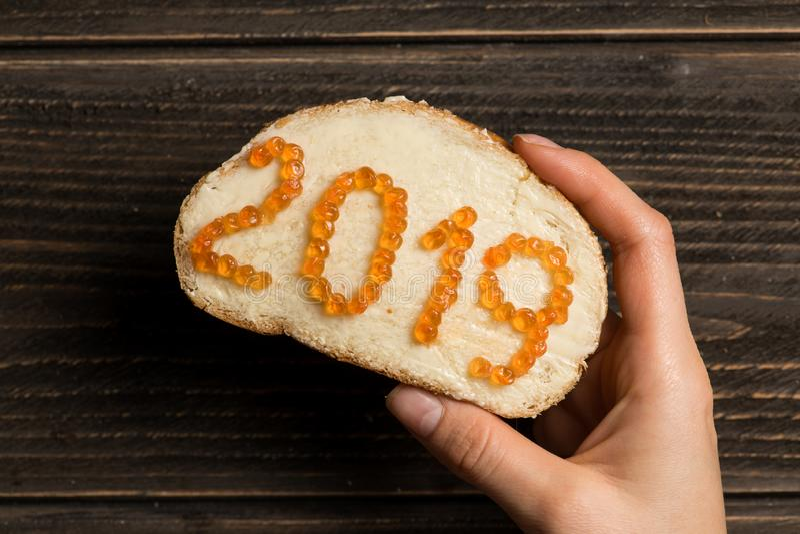 Mão da mulher que guarda um sanduíche com a manteiga e o caviar vermelho colocados sob a forma de 2019 imagem de stock royalty free