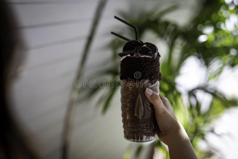 Mão da mulher que guarda uma agitação e cookies de chocolate em um vidro transparente com projeto aborígene fotos de stock royalty free