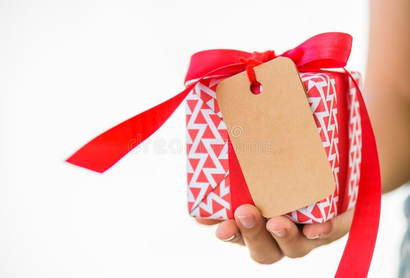 Mão da mulher que guarda uma caixa de presente vermelha com espaço da cópia do cartão de etiquetas fotos de stock royalty free