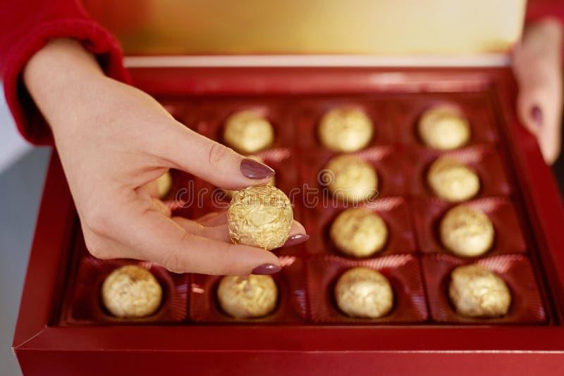 Mão da mulher que guarda uma parte do chocolate na caixa para o dia de são valentim imagem de stock royalty free