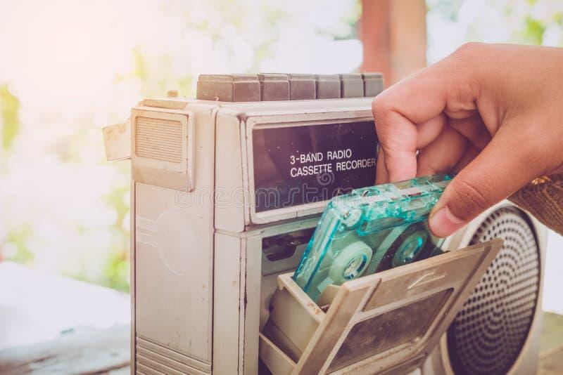 A mão da mulher que guardam a gaveta de fita com leitor de cassetes e o registrador para escutam música fotografia de stock