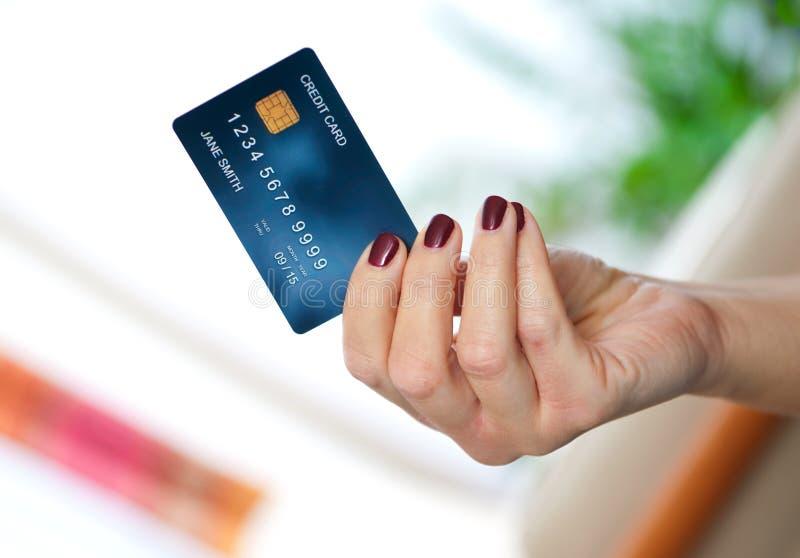 Mão da mulher que guardara o cartão de crédito foto de stock royalty free