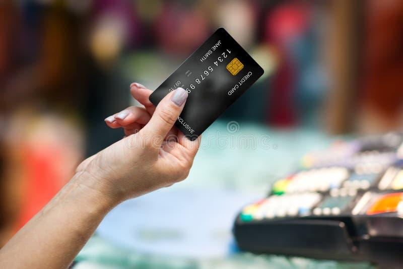 Mão da mulher que guardara o cartão de crédito fotografia de stock royalty free