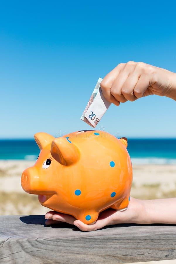 A mão da mulher que introduz a nota do Euro em Piggybank na praia imagem de stock