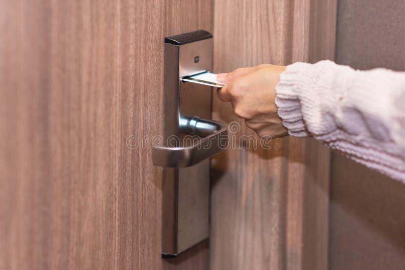 Mão da mulher que introduz o cartão para abrir o fechamento eletrônico na porta do hotel fotos de stock royalty free