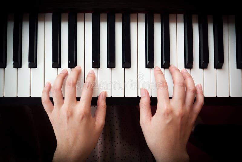 A mão da mulher que joga o piano imagens de stock royalty free