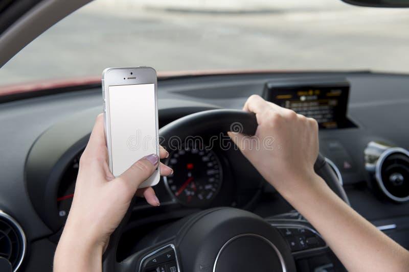 Mão da mulher que mantém o volante e o telefone celular que conduzem o carro ao texting confundido no risco imagem de stock royalty free