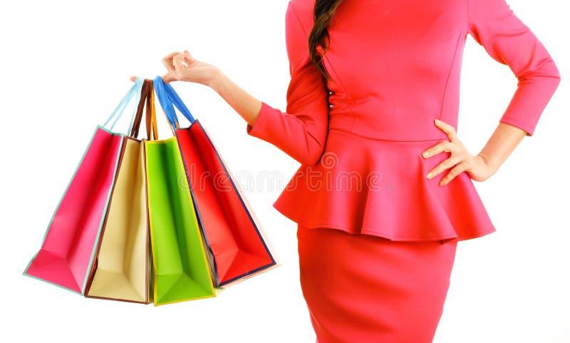 A mão da mulher que mantém os sacos de compras de papel isolados no branco imagens de stock