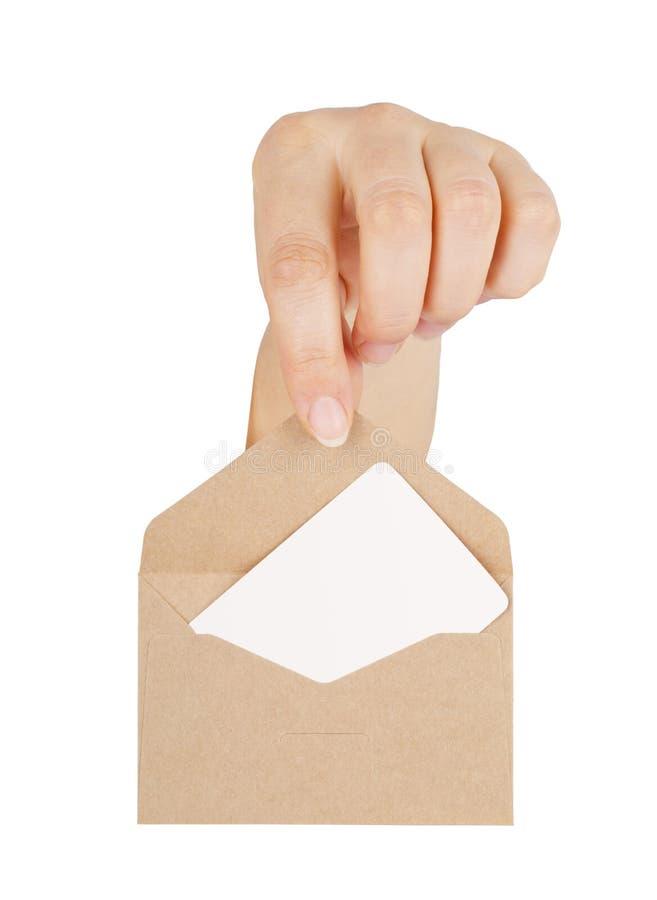 A mão da mulher que mantém um envelope com um cartão isolado foto de stock