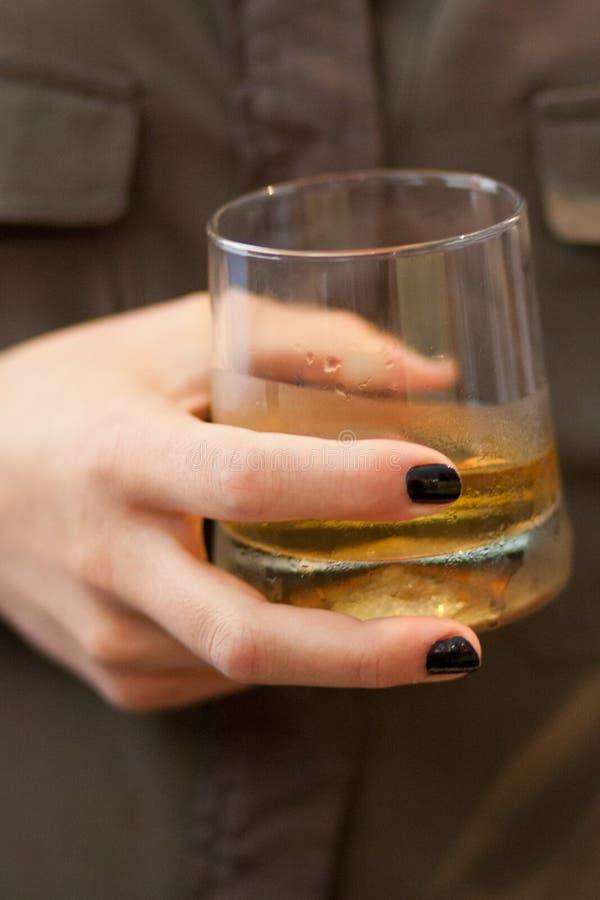 Mão da mulher que mantém um uísque de vidro foto de stock