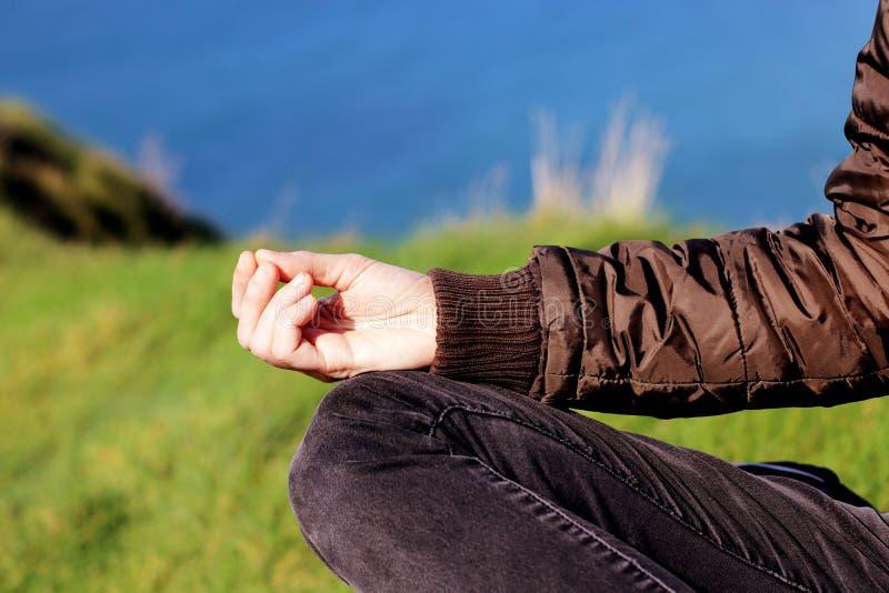 Mão da mulher que medita na pose da ioga sobre penhascos na primavera no por do sol fotografia de stock royalty free