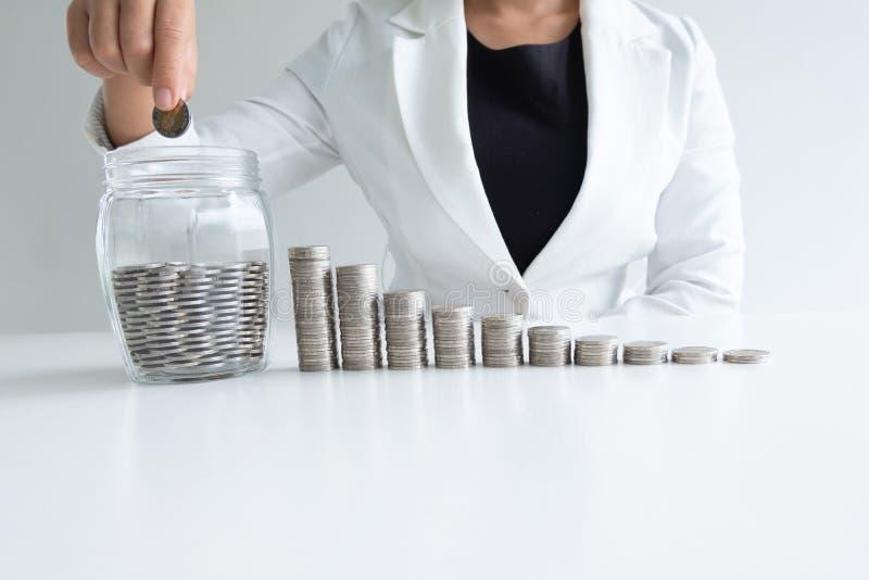 Mão da mulher que põe a moeda no banco da garrafa de vidro com gráfico de barra das moedas fotografia de stock