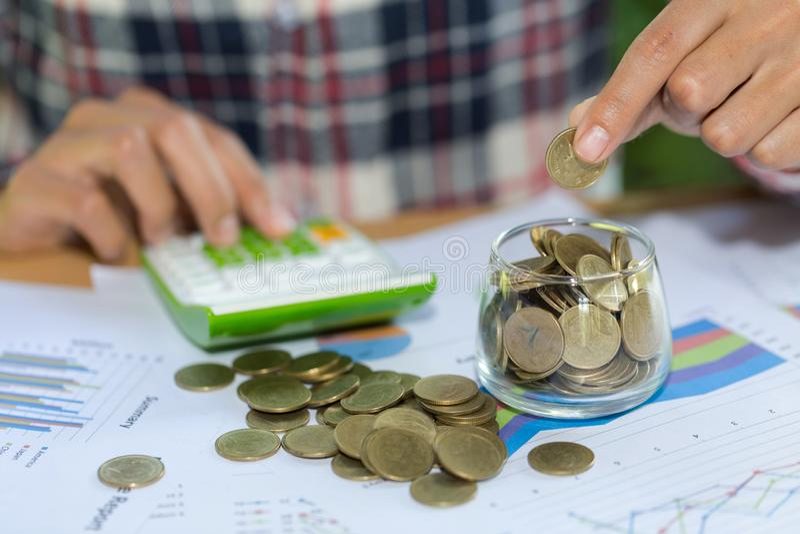 Mão da mulher que põe o coinIn o frasco de vidro Riqueza de salvamento do dinheiro e conceito financeiro, finança pessoal, gestão imagens de stock