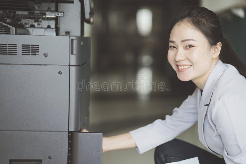 Mão da mulher que põe uma folha de papel em um copi imagem de stock royalty free