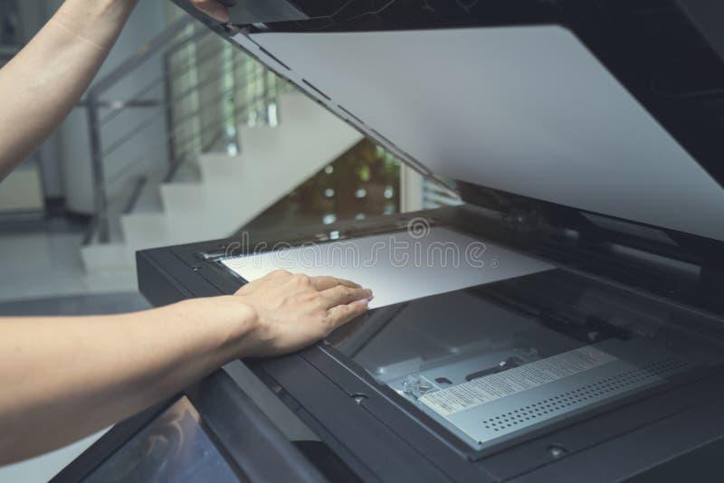 Mão da mulher que põe uma folha de papel em um dispositivo de copi imagens de stock