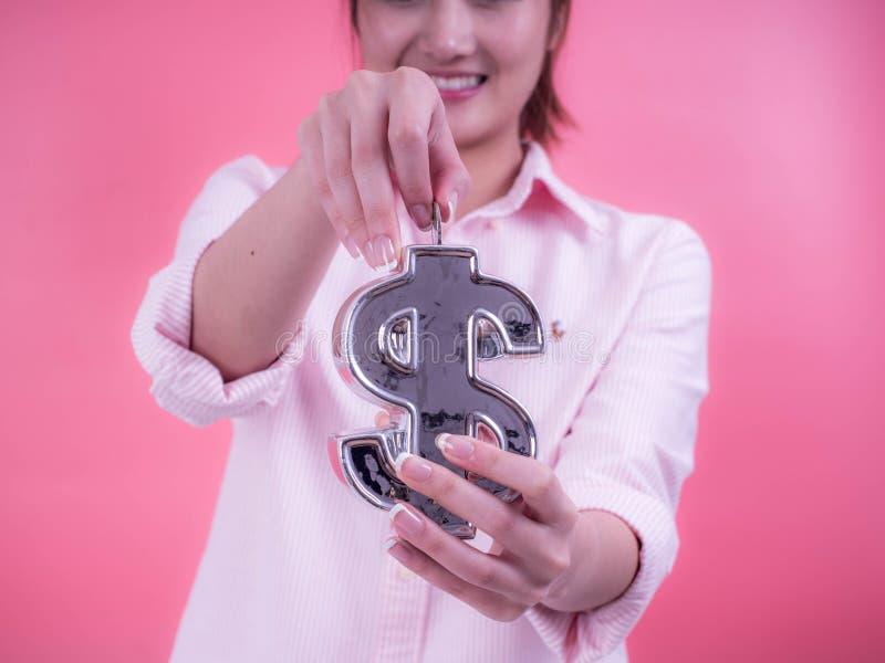 Mão da mulher que põe uma moeda no banco financeiro do símbolo Conceito do futuro, do negócio, do dinheiro de salvamento, da econ fotos de stock royalty free