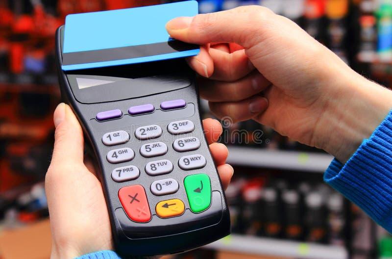 Mão da mulher que paga com o cartão de crédito sem contato, tecnologia de NFC foto de stock
