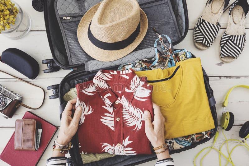 Mão da mulher que prepara a bagagem do verão fotografia de stock