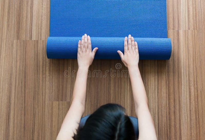 Mão da mulher que rola ou que dobra a esteira azul da ioga após um exercício, um equipamento do exercício, uma aptidão da vista s fotografia de stock royalty free