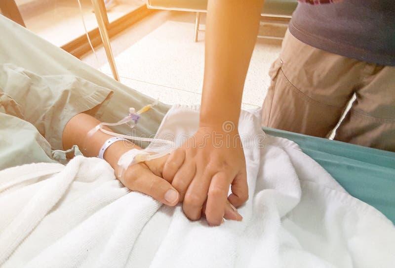 Mão da mulher que toca junto em pacientes de cama na clínica, mãos imagens de stock