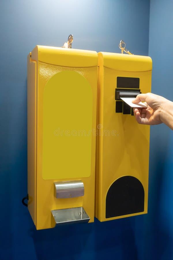 A mão da mulher que toma o cartão da máquina do cambiador de conta na cor amarela imagens de stock