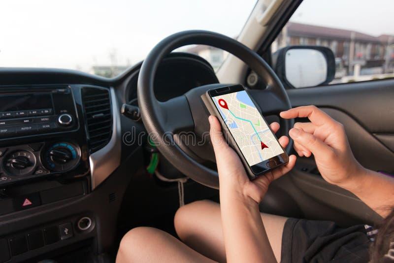 Mão da mulher que usa o smartphone com o applicatio do mapa do navegador dos gps imagem de stock