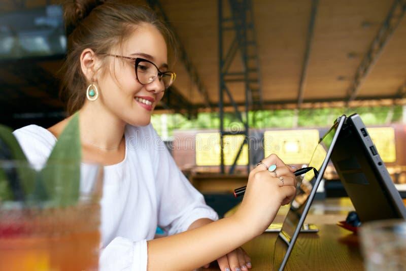 Mão da mulher da raça misturada do Freelancer que aponta com o estilete na tela convertível do portátil no modo da barraca Menina fotos de stock