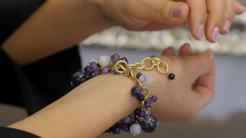 Mão da mulher s - dos tipos gemas para fora no bracelete da joia imagem de stock