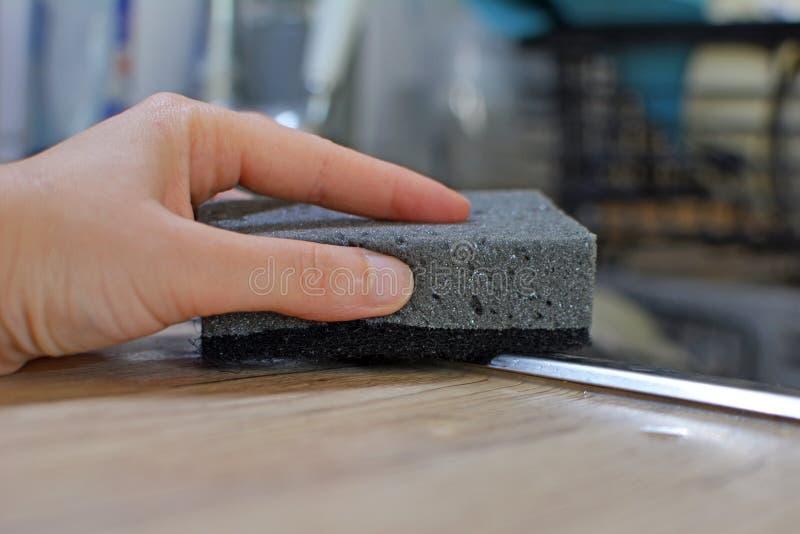 Mão da mulher sem luvas que limpam a banca da cozinha com a esponja cinzenta fotos de stock royalty free