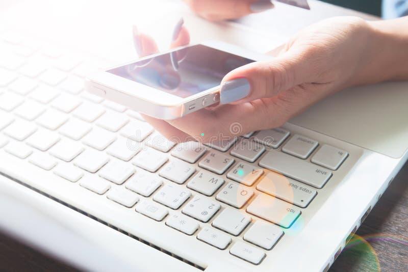 Mão da mulher usando o dispositivo móvel e o portátil em sua mesa, compra em linha fotos de stock royalty free