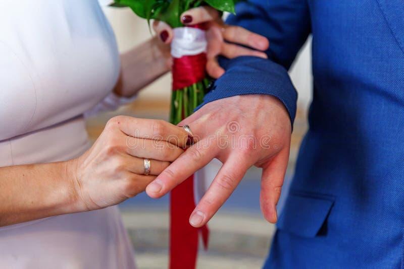 Mão da noiva que põe a aliança de casamento sobre o dedo do noivo imagem de stock royalty free