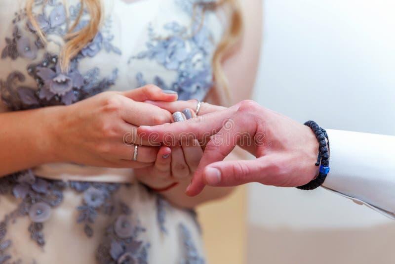 Mão da noiva que põe a aliança de casamento sobre o dedo do noivo fotografia de stock royalty free