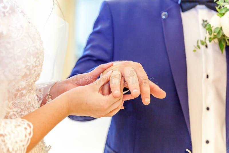 Mão da noiva que põe a aliança de casamento sobre o dedo do noivo foto de stock royalty free