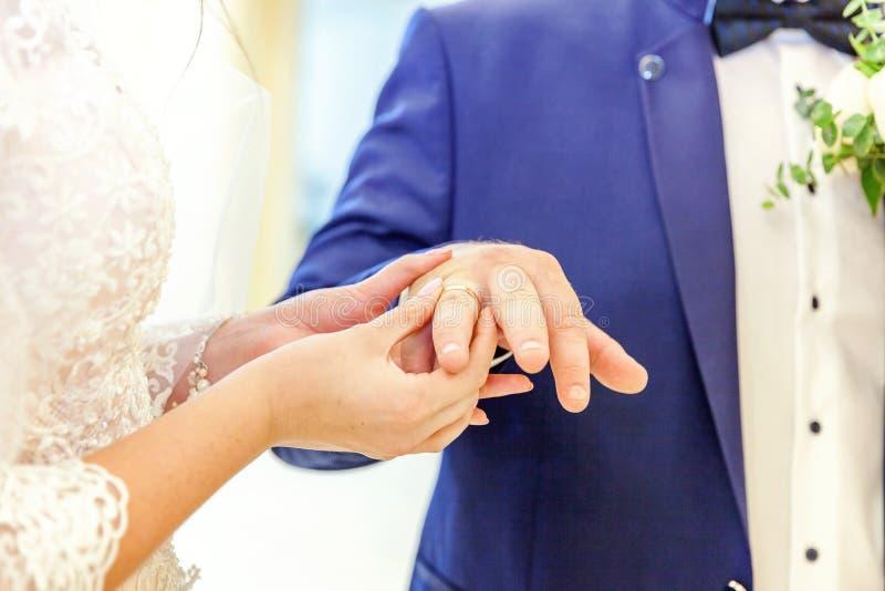Mão da noiva que põe a aliança de casamento sobre o dedo do noivo imagem de stock