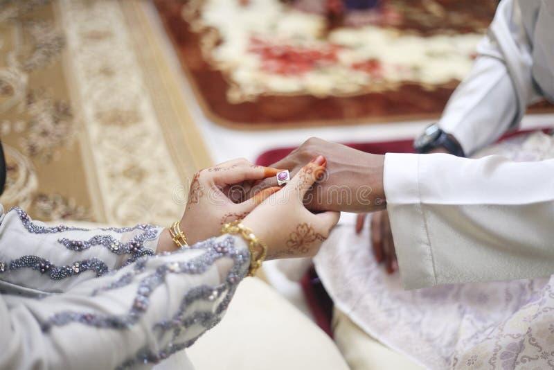 Mão da noiva que põe uma aliança de casamento sobre o dedo do noivo imagens de stock