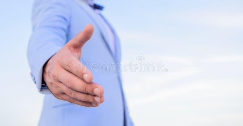 Mão da mão da oferta do homem de negócios para o fundo do céu azul do aperto de mão Gesto ou oportunidade amigável do aperto de m imagem de stock