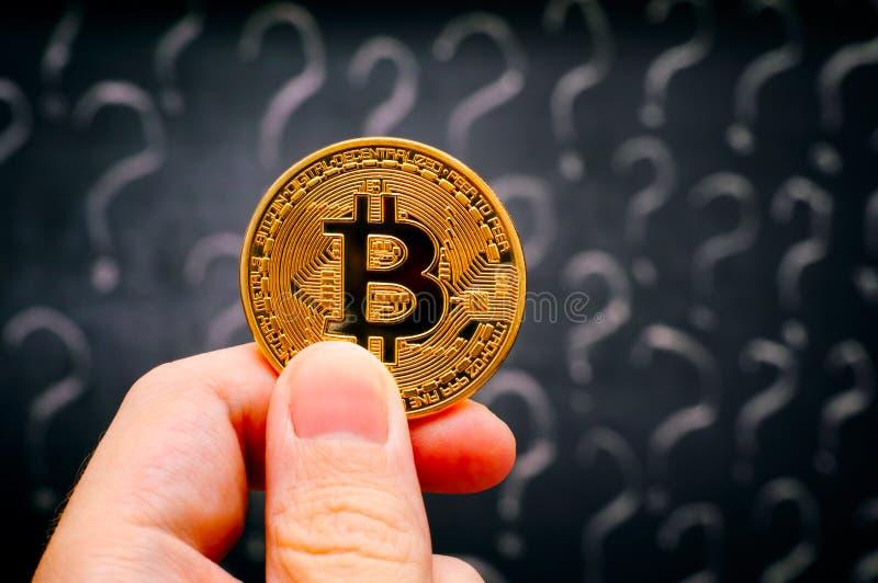 Mão da pessoa com dinheiro virtual de Bitcoin contra o quadro-negro com pontos de interrogação imagem de stock