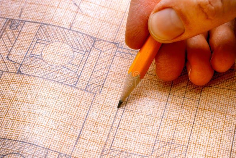 Mão da pessoa com lápis e o desenho técnico foto de stock